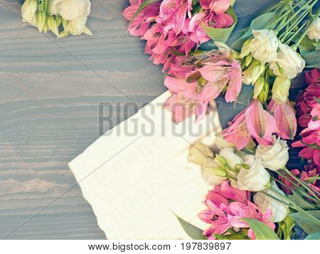 Beautiful background of red and pink Alstroemeria and white eustoma flowers on wooden background. Tinted Windows. Copy space. The horizontal frame.