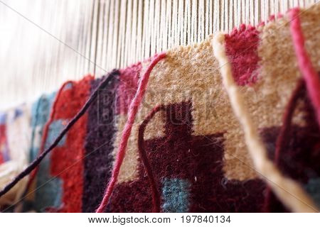 Weaving a carpet on a  traditional loom