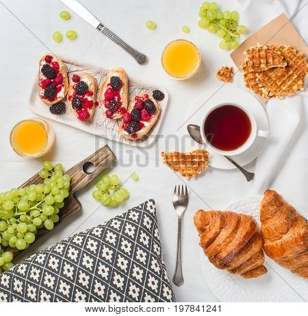 Breakfast in bed with croissants raspberry and blackberry bruschetta. Morning treat concept.