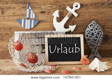 Blackboard With Nautical Summer Decoration And Wooden Background. German Text Urlaub Means Holiday. Fish, Anchor, Shells And Fishnet For Maritime Contex.
