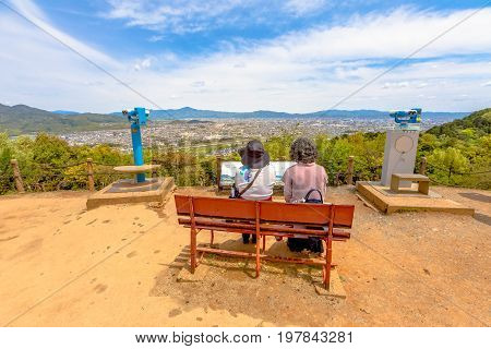 Kyoto, Japan - April 27, 2017: senior visitors sitting on benche of popular attraction touristic Iwatayama Monkey Park in Arashiyama, Kyoto, admiring spectacular skyline of Kyoto from top of the park.