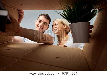 A young couple unpacks boxes. The concept of moving, housewarming.