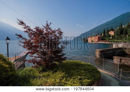 Panoramic view of Como lake shore and Bellano fishing village. Italian waterfront houses, wooden pier and mountains in small coast town Bellano, Lombardi, Italy.