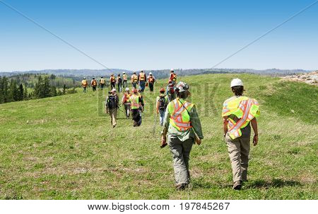 Group of workers and geologists in hardhats and high visible vests inspecting site. View from the back. Walking across grass field.