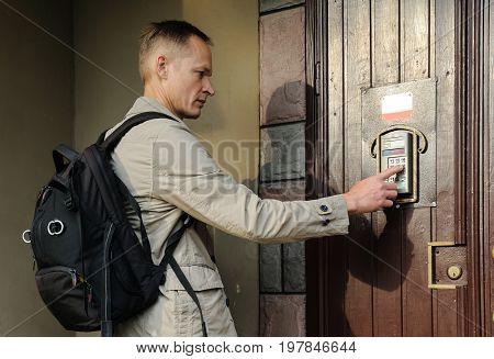 The man is dialing the code on the door intercom of the front door.