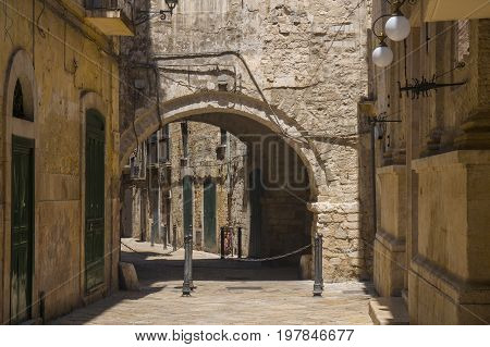 Narrow street with an arch in the old town of Bari, Puglia, Italy.