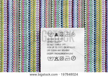 Washing instructions label on colorful textile background