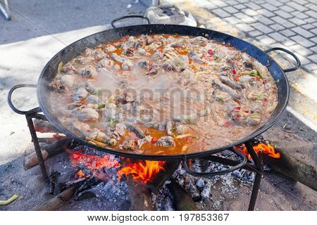 Paella. The national Spanish dish of paella in a large skillet is cooked on an open fire, at the stake