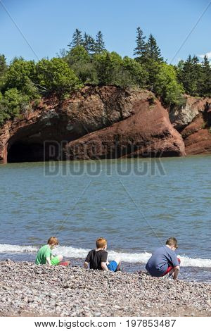 Boys playing on the shoreline of the Bay of Fundy seacaves, New Brunswick, Canada
