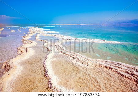 Hot summer day at the seaside resort on the Dead Sea, Israel. The evaporated salt has developed into fantastic patterns. The concept of medical and ecological tourism