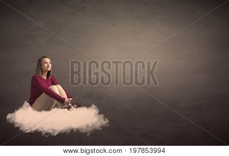 Caucasian woman sitting on a white fluffy cloud daydreaming beside a plain grunge background
