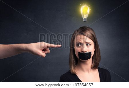 Caucasian hand pointing at female employee with a lightbulb above her head