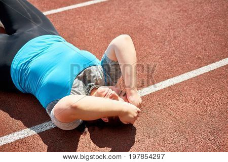 Exhausted sweaty over-size woman trying to do difficult exercise on race track