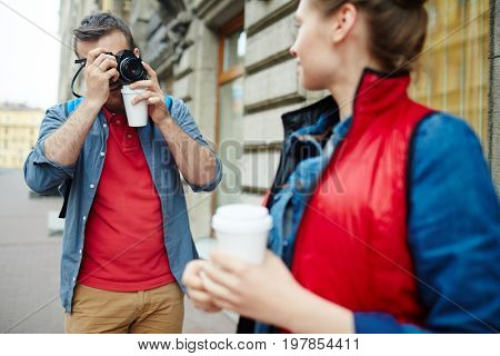 Guy with photocamera shooting his girlfriend during their journey