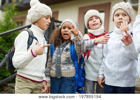 Group of little kids with rucksacks having talk after classes