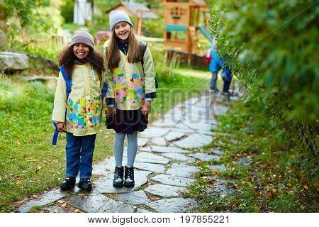 Friendly schoolgirls in yellow raincoats going to school