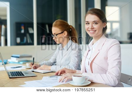 Female analyst reading paper documents with colleague on background