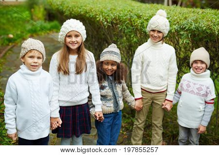 Affectionate schoolmates in casual knitwear