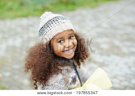 African-american girl in knitted beanie hat and cardigan