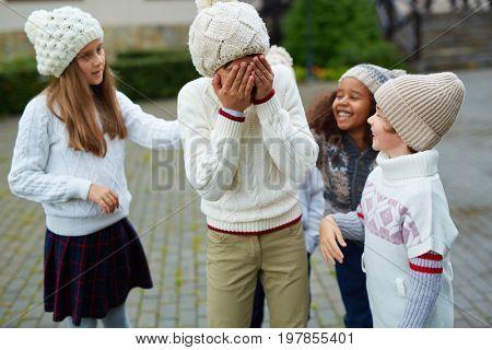 Laughing kids making fun of their classmate