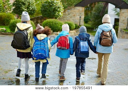 Schoolkids in casualwear with rucksacks behind backs holding by hands while going to school