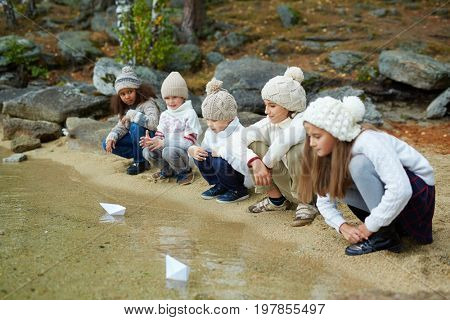 Little friends looking at paper ships floating on water surface
