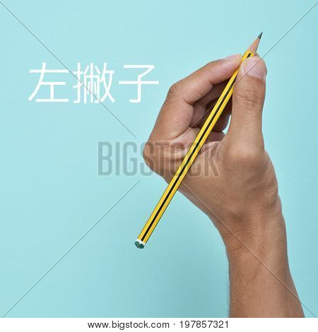 the text left-hander or left-handedness written in Chinese and the hand of a left-handed man with a pencil, against a blue background
