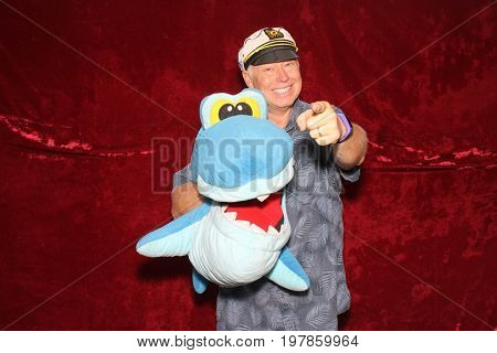 A man poses for photos in a Photo Booth. A man wears a Captain Hat and holds a Stuffed Shark and points while in a photo booth.