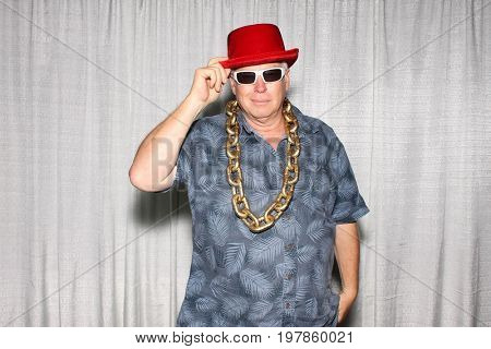 A man poses for photos in a Photo Booth. A man wears a red had, sunglasses and smiles while in a photo booth with white curtains.