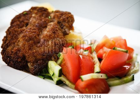 Minced meat cutlet with boiled potatoes and tomato-cucumber salad