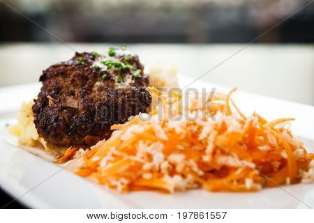 Minced beef cutlet with mashed potatoes in creamy sauce and carrot-cabbage salad