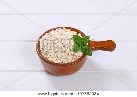 saucepan of puffed buckwheat on white wooden background