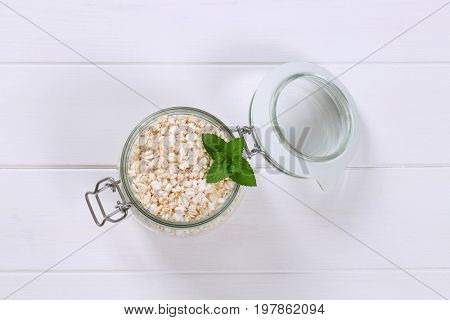 jar of puffed buckwheat on white wooden background