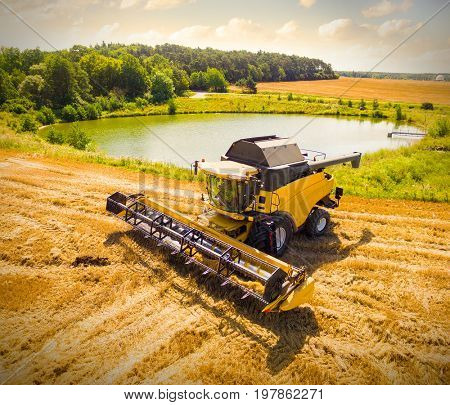 Aerial view of combine harvester. Harvest of wheat field. Czech rural landscape in summer. Bio production from above. Agriculture and environment in European Union.