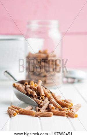 Dried rigatoni pasta in scoop on white table. Dark semolina pasta.