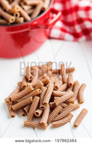 Dried rigatoni pasta on white table. Dark semolina pasta. Uncooked pasta.