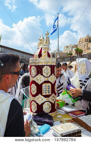 JERUSALEM, ISRAEL - OCTOBER 12, 2014: Sukkot. The area in front of Western Wall of Temple filled with people. Imposition of a Sefer Torah for prayer.  Jews of ritual tallit worship with prayer books