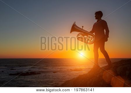 Silhouette of musician with trumpet on rocky sea coast during sunset. Tuba.