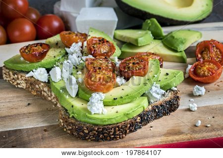 Avocado toast with roasted cherry tomatoes and feta cheese.