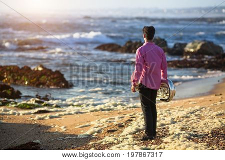 View from the back young musician play trumpet on rocky sea coast during surf. Tuba instrument.