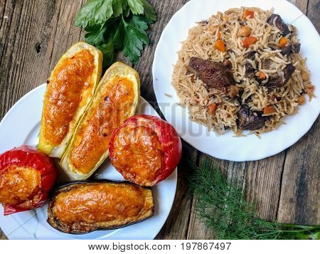 Baked vegetables - tomato, eggplant, zucchini - with cheese and egg stuffing and traditional Uzbek dish of pilaf