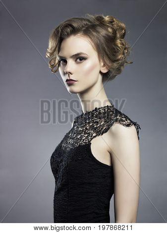 Studio fashion photo of beautiful young lady on black background. Classic studio portrait. Elegant hairstyle