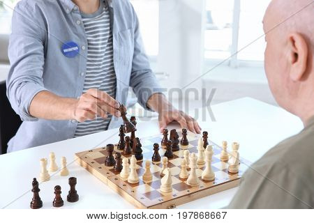 Young male volunteer playing chess with elderly man in light room