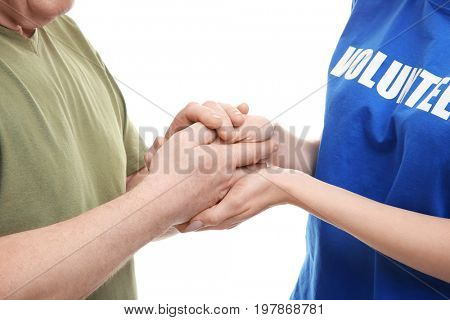Young female volunteer and senior man holding hands on white background