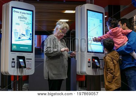 Coquitlam, BC, Canada - April 11, 2017 : Family ordering food at self check out machine and old lady playing cellphone at Mcdonalds restaurant