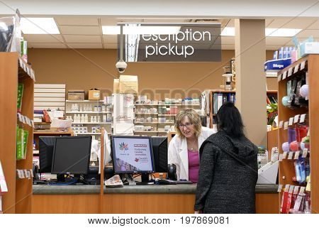 Port Coquitlam, BC, Canada - April 11, 2017 : People picking up her prescription medicine at pharmacy section in Port Coquitlam BC Canada