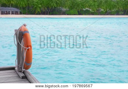 Wooden pontoon with flotation ring at tropical resort on summer day