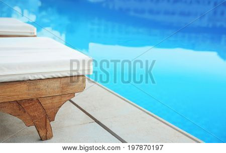 Modern swimming pool with chaise lounges in luxury hotel