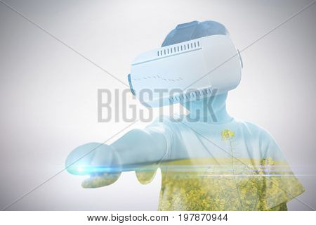 Boy clenching fist while using virtual reality glasses against beautiful mustard field