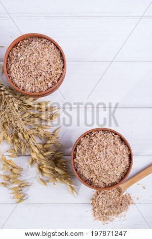 Wheat, Oat bran in clay  bowl and ears of wheat and oat.  Dietary supplement to improve digestion. On white background. Flat lay.